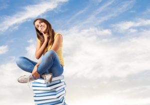 young pretty woman thinking and sitting on abig books pile